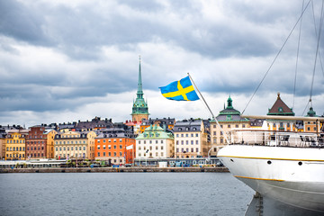 In de dag Stockholm Swedish flag on the boat against Stockholm old city. Panoramic view of Gamla Stan from Baltic Sea, Sweden.
