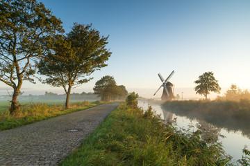Windmill during a foggy, autumn sunrise in the Dutch countryside. Krimstermolen, Zuidwolde.