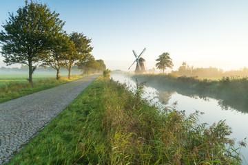 Dutch countryside with a windmill on a foggy morning. Krimstermolen, Zuidwolde.