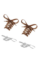 The photo of light golden shiny shoelaces with golden tips, hanging in the air on a white background. Shoelaces is casting a shadow.