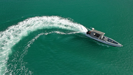 Aerial top view luxury inflatable rib speed boat cruising in mediterranean emerald bay with crystal clear sea