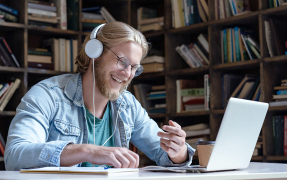 Happy male student online teacher laugh wear headphone talk video calling on laptop computer having fun communicate with skype tutor concept, distance education e learning chat course in library