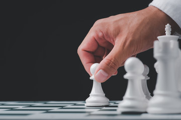 Businessman hand play with chess game. concept of business strategy and tactic.strategy, management or leadership concept