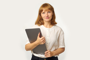 Headshot of young woman with red hair and freckles holding laptop and looking directly to the camera with a friendly smile