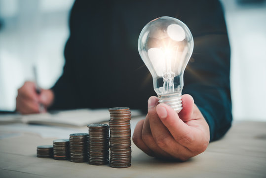 businessman hand holding lightbulb with coins stacking on desk.saving energy and money concept.