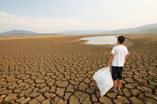 Young man holding full plactic bags while looking to the drying lake metaphor Drought and Plastic pollution in the water