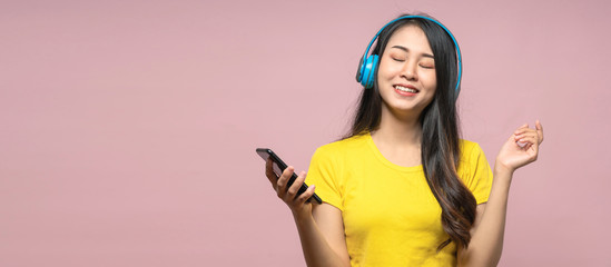 Banner of Happy chill asian girl listening to music in wireless headphone with smartphone. Woman listening podcast and wearing yellow shirt on pink isolated background.