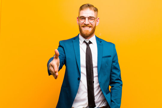 young red head businessman smiling, looking happy, confident and friendly, offering a handshake to close a deal, cooperating against orange background