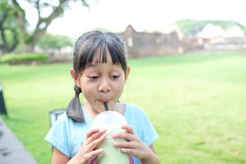 Girls enjoy sucking green tea drinks.