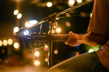 Rear view of the man sitting play acoustic guitar on the outdoor concert with a microphone stand in the front, musical concept. Fotobehang