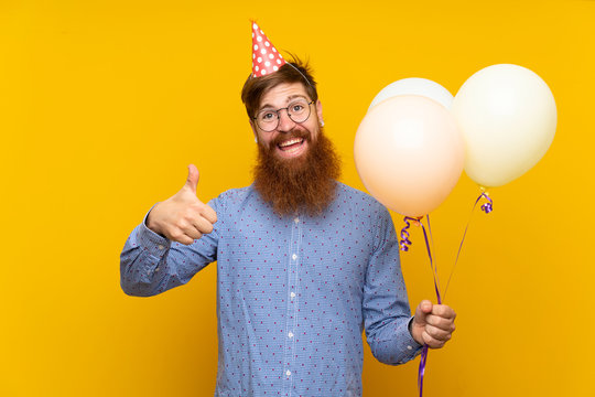 Redhead man with long beard holding balloons over isolated yellow background with thumbs up because something good has happened