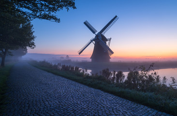 Windmill during a foggy, autumn dawn in the Dutch countryside. Krimstermolen, Zuidwolde.