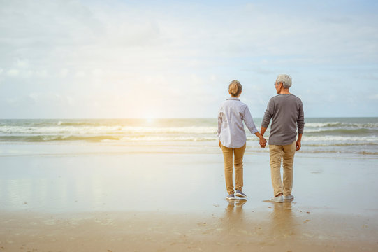 Senior couple standing on the beach holding hands at sunrise, plan life insurance at retirement concept.
