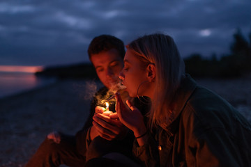 Couple lighting joint at night in nature