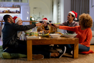 Millennial adult friends celebrating Christmas together at home