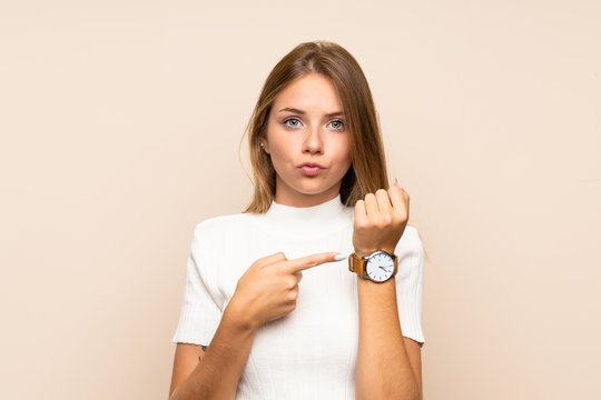 Young blonde woman over isolated background showing the hand watch with serious expression