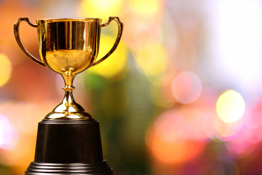Gold trophy cup on full color background with bokeh