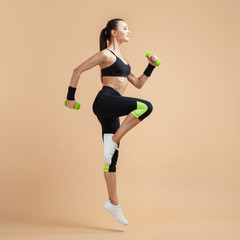 A young brunette woman is engaged in fitness, jumping with dumbbells, raising her knees high, on a peach background.