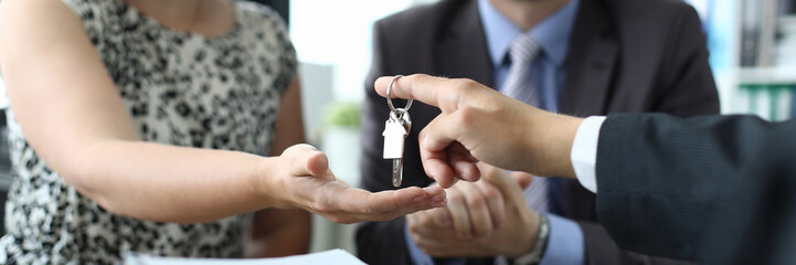 Focus on male hand giving bunch to happy woman. Smiling husband and wife in modern office of estate agent. Buying property concept. Blurred background