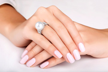 Wall Mural - Beautiful female hands with diamond ring with pearl. Beautiful woman's nails with manicure. Diamond ring with pearl. White gold.