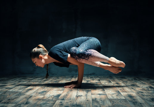 Young attractive woman practicing yoga doing side crane pose in dark room