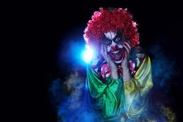 Screaming scary clown against blue light