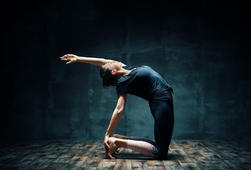 Young attractive woman practicing yoga doing half camel pose in dark room