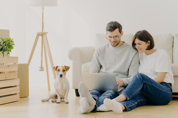 Beautiful couple with dog sit on floor in spacious living room, make purchasing online, buy furniture for new home, have to unpack belongings, have happy expression, start living together in new flat
