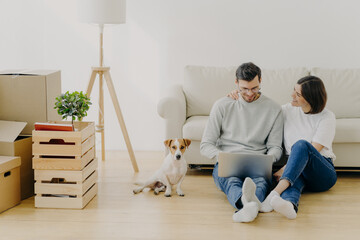 Lovely husband and wife sit in new apartment with laptop computer, discuss home repair project, pose in living room with sofa, stack of boxes and pedigree dog. Moving and relocation concept.