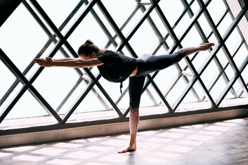 Young attractive woman practicing yoga doing Warrior 3 Pose large triangular window background