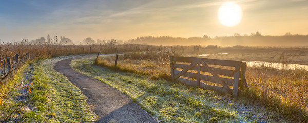 Foto op Canvas Landschappen Gate in misty agricultural landscape