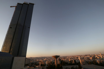 A tower block that is under construction is seen against the Amman cityscape in the evening light in Amman