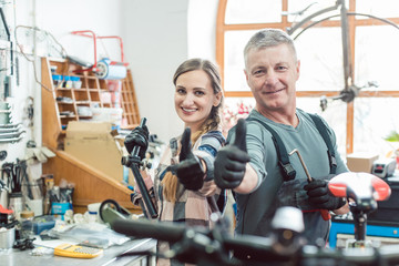 Two bike mechanics in their workshop having a successful day