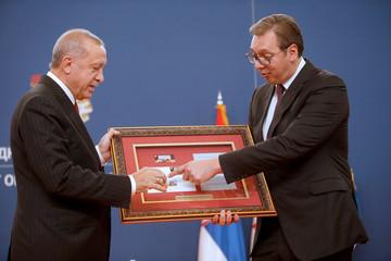Turkish President Tayyip Erdogan exchanges gifts with Serbia's President Aleksandar Vucic after their meeting in Belgrade