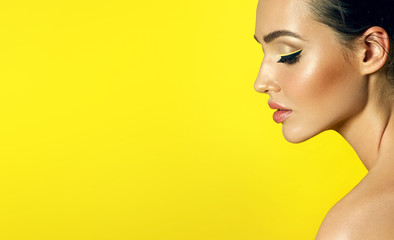 Face in profile close-up on a yellow background of a beautiful young girl with perfect smooth skin and bright eye make-up. Fototapete