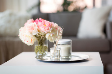 decoration, hygge and cosiness concept - aroma reed diffuser, candle and flower bunch on wooden table