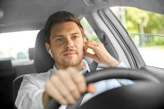 transport, vehicle and people concept - man or driver with wireless earphones or hands free device driving car