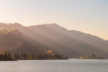 Sunset light streams through the hollows of the hills along the Columbia River near Mosier, Oregon