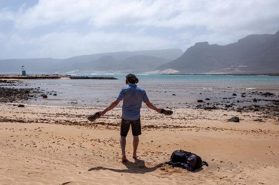 Man shakes the sand off from his shoes at the beach (Baia das Gatas, Sao Viente Island in Cape Verde)