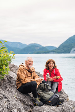 A senior pensioner couple hiking by lake in nature, sitting and resting.