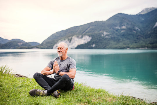 A senior man pensioner sitting by lake in nature, doing yoga exercise.