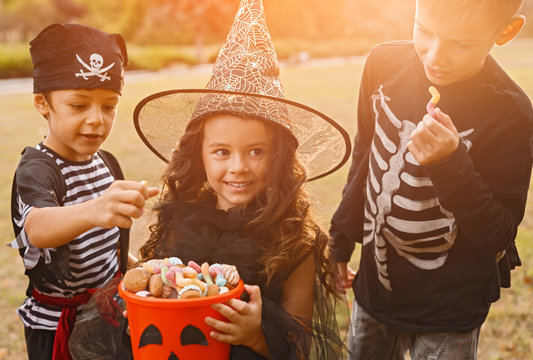 Happy kids in Halloween costumes with candy collector