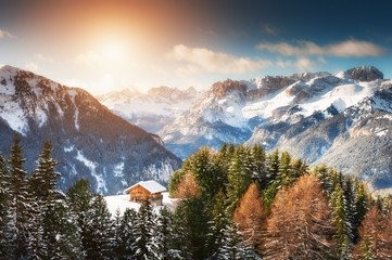 Wooden house in winter mountains at sunset. Ski resort in Dolomite Alps. Val Di Fassa, Italy. Beautiful winter landscape Fototapete