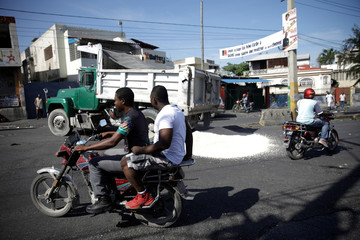 People riding motorbikes drive next to a pile of sand being unloaded from a truck to set a barricade in a protest to demand the resignation of Haitian president Jovenel Moise, in the streets of Port-au-Prince