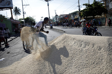 A protester shovels sand after a truck unloaded it to set a barricade to demand the resignation of Haitian president Jovenel Moise, in the streets of Port-au-Prince