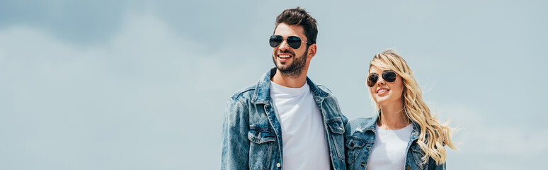 Fotomurales - panoramic shot of attractive woman and handsome man in denim jackets smiling outside