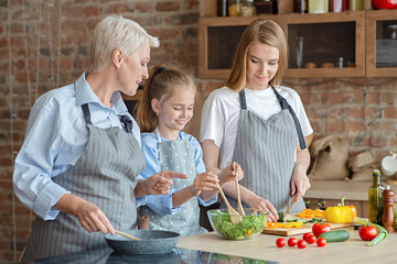 Cute little girl mixing salad under mom and granny supervision