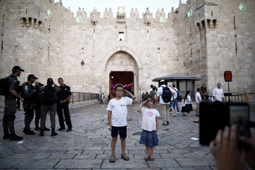 A woman takes a photograph of children as they pose near Damascus Gate in Jerusalem's Old City