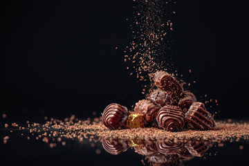 Chocolate candies on a black background sprinkled with chocolate chips.