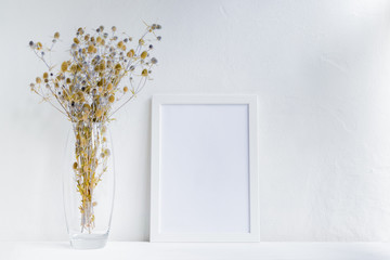 Mockup with a white frame and dry flowers in a vase on a white table